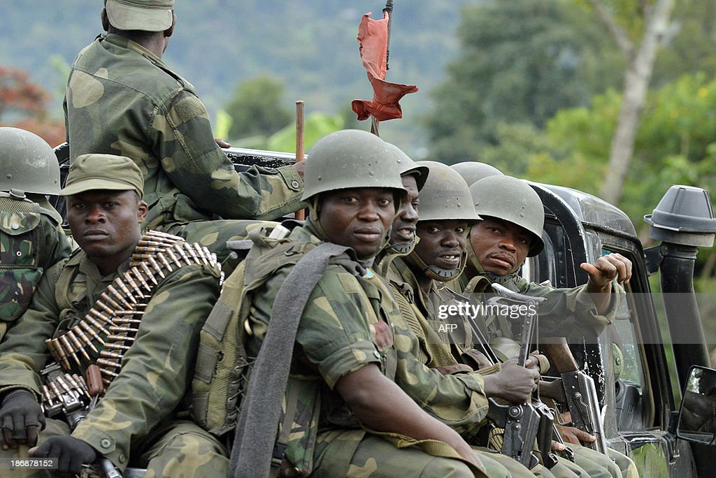 Democratic Republic of Congo Fardc regular army soldiers sit at the back of a pick-up truck as they head towards the Mbuzi hilltop, near Rutshuru, on November 4, 2013, after the army recaptured the area from M23 rebels. Democratic Republic of Congo troops have driven out M23 rebels from several key positions in the east of the country in recent weeks, pushing on with an assault despite calls for a truce. Meanwhile African leaders will meet late on November 4 to discuss the next steps for a major peacekeeping mission in the Democratic Republic of Congo, as rebels there are forced onto the back foot. AFP PHOTO / Junior D. Kannah