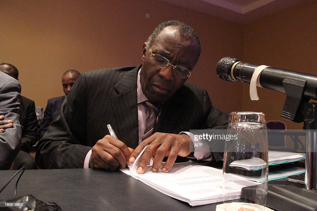 Democratic Republic of Congo Foreign Minister Raymond Tshibanda signs documents on February 6, 2013 before a press conference in Kampala. The government of the Democratic Republic of Congo and M23 rebels holding peace talks in Kampala on February 6 finalized a review of an earlier failed peace agreement, the first of four stages toward reaching a peace deal. M23 rebels were persuaded to withdraw from the key eastern city of Goma after a 12-day occupation, they still control large areas of territory just outside the strategic mining hub. The negotiations are the latest in several bids to end a long-running conflict that has forced hundreds of thousands of people in eastern DR Congo from their homes. AFP PHOTO/ ISAAC KASAMANI