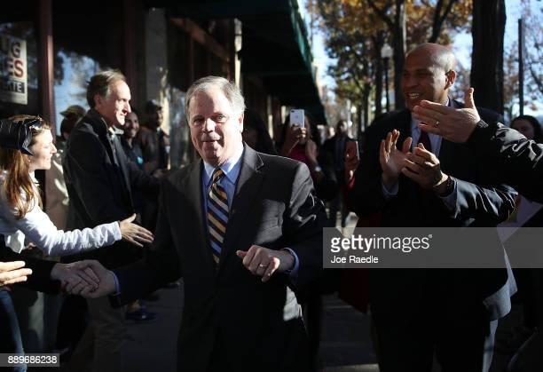 Democratic Senatorial candidate Doug Jones arrives with US Sen Cory Booker at a Jones for Senate Field Office on December 10 2017 in Birmingham...