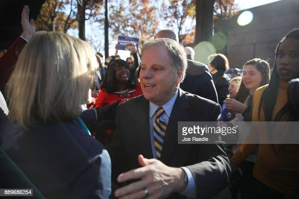 Democratic Senatorial candidate Doug Jones greets people as he arrives for a campaign stop at a Jones for Senate Field Office on December 10 2017 in...