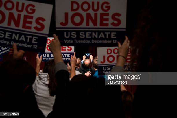Democratic Senatorial candidate Doug Jones takes a selfie with supporters after speaking at a rally in Birmingham Alabama on December 9 2017 The...