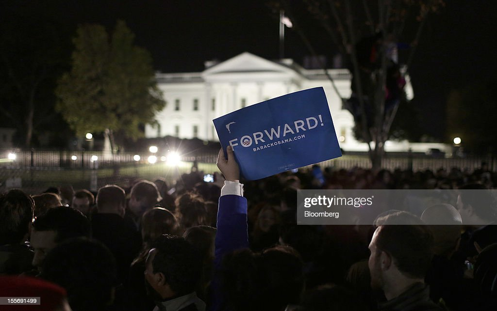 A Democratic supporter holds a 'Forward' sign as people gather to celebrate U.S. President Barack Obama's re-election in front of the White House in Washington, D.C., U.S., on Wednesday, Nov. 7, 2012. Obama, the post-partisan candidate of hope who became the first black U.S. president, won re-election today by overcoming four years of economic discontent with a mix of political populism and electoral math. Photographer: Joshua Roberts/Bloomberg via Getty Images