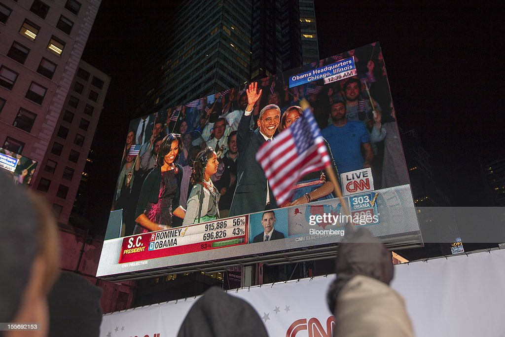 A Democratic supporter waves a flag while watching U.S. President <a gi-track='captionPersonalityLinkClicked' href=/galleries/search?phrase=Barack+Obama&family=editorial&specificpeople=203260 ng-click='$event.stopPropagation()'>Barack Obama</a> prepare to give his acceptance speech on a screen at Times Square in New York, U.S., early on Wednesday, Nov. 7, 2012. Obama, the post-partisan candidate of hope who became the first black U.S. president, won re-election today by overcoming four years of economic discontent with a mix of political populism and electoral math. Photographer: Michael Nagle/Bloomberg via Getty Images