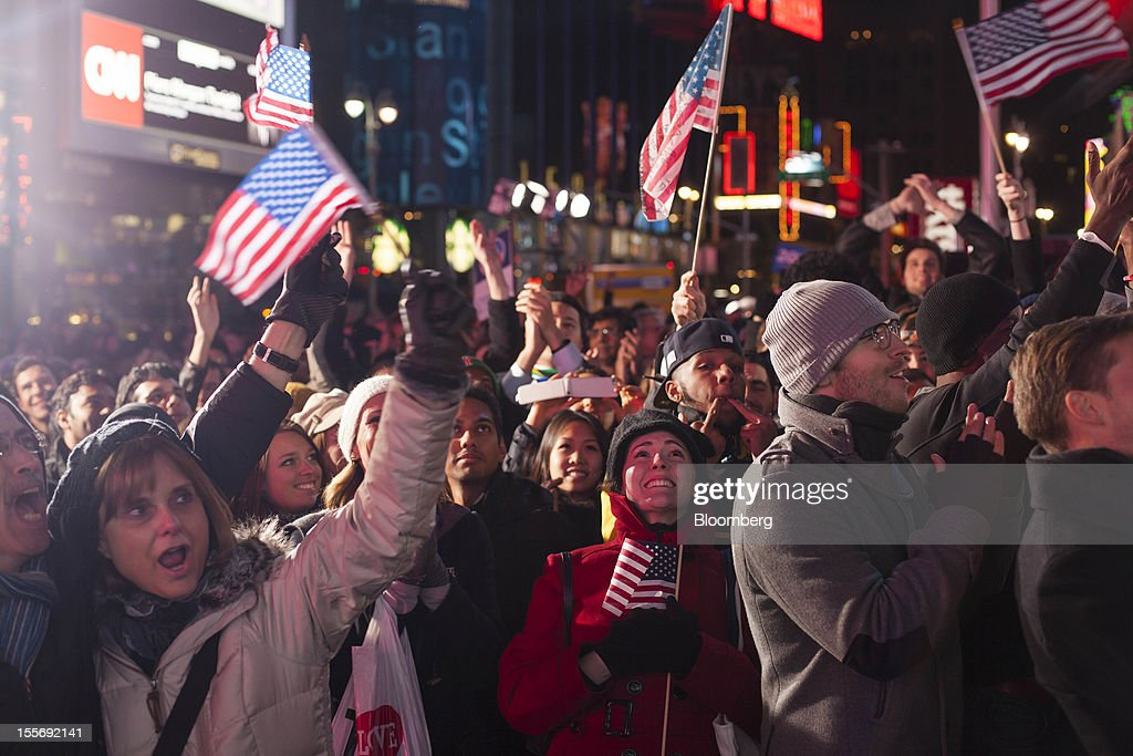 Democratic supporters celebrate after watching U.S. President Barack Obama give his acceptance speech on a screen at Times Square in New York, U.S., early on Wednesday, Nov. 7, 2012. Obama, the post-partisan candidate of hope who became the first black U.S. president, won re-election today by overcoming four years of economic discontent with a mix of political populism and electoral math. Photographer: Michael Nagle/Bloomberg via Getty Images