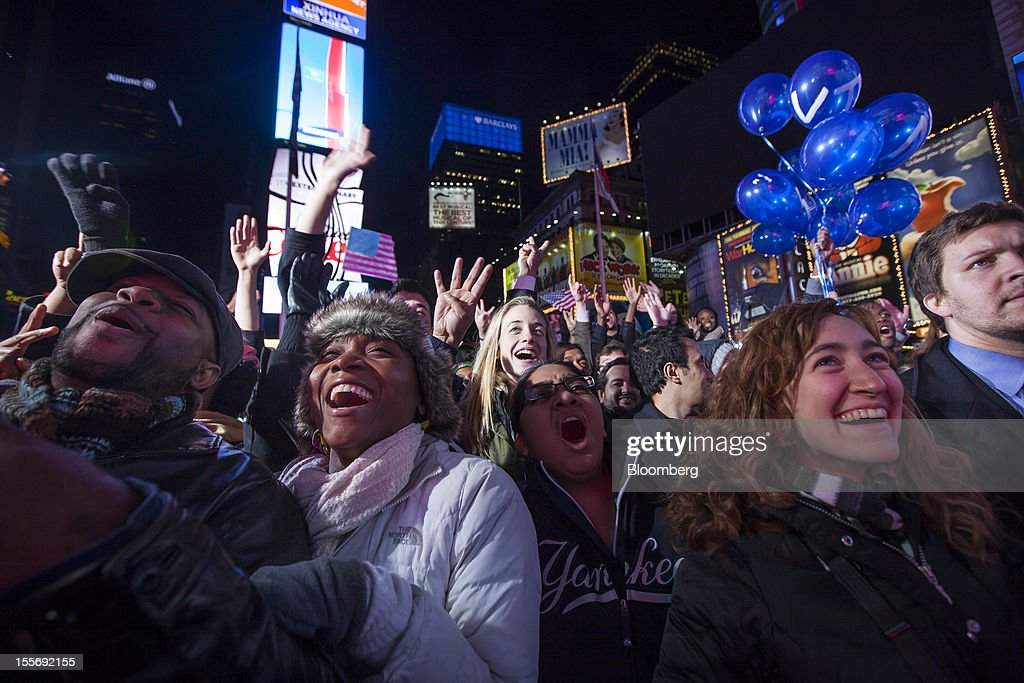 Democratic supporters celebrate as they watch U.S. President Barack Obama give his acceptance speech on a screen at Times Square in New York, U.S., early on Wednesday, Nov. 7, 2012. Obama, the post-partisan candidate of hope who became the first black U.S. president, won re-election today by overcoming four years of economic discontent with a mix of political populism and electoral math. Photographer: Michael Nagle/Bloomberg via Getty Images