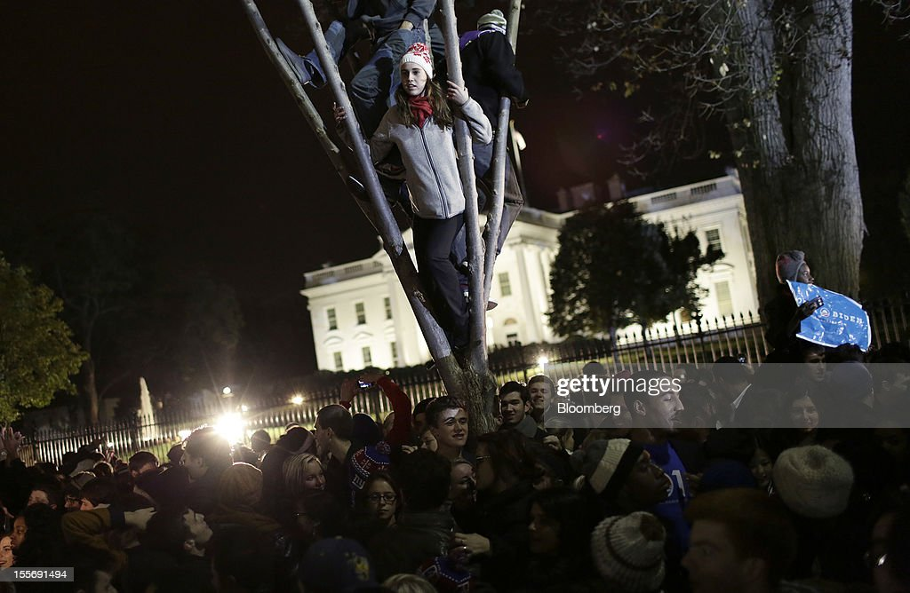 Democratic supporters celebrate U.S. President Barack Obama's re-election in front of the White House in Washington, D.C., U.S., on Wednesday, Nov. 7, 2012. Obama, the post-partisan candidate of hope who became the first black U.S. president, won re-election today by overcoming four years of economic discontent with a mix of political populism and electoral math. Photographer: Joshua Roberts/Bloomberg via Getty Images