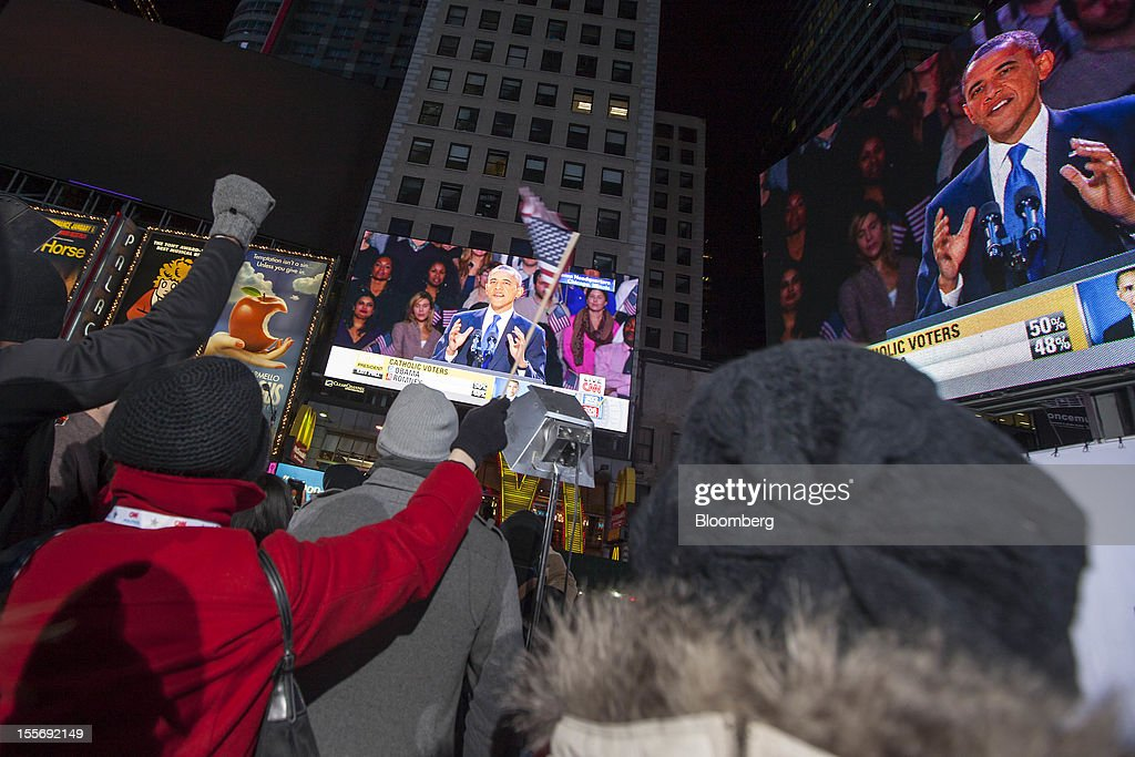 Democratic supporters watch U.S. President Barack Obama give his acceptance speech on a screen at Times Square in New York, U.S., early on Wednesday, Nov. 7, 2012. Obama, the post-partisan candidate of hope who became the first black U.S. president, won re-election today by overcoming four years of economic discontent with a mix of political populism and electoral math. Photographer: Michael Nagle/Bloomberg via Getty Images