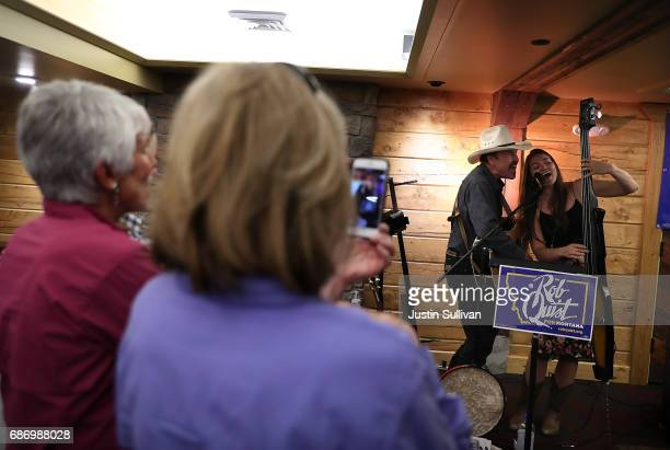 Democratic US Congressional candidate Rob Quist performs a song with his daughter Halladay Quist during a gathering with supporters at Darkhorse Hall...