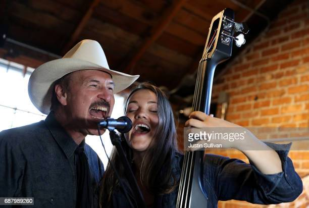 Democratic US Congressional candidate Rob Quist sings with his daughter Halladay Quist during a campaign rally at Draught Works Brewery on May 24...