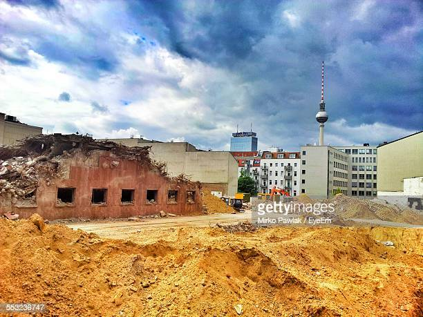 Demolished Buildings With Cityscape In Background Against Cloudy Sky