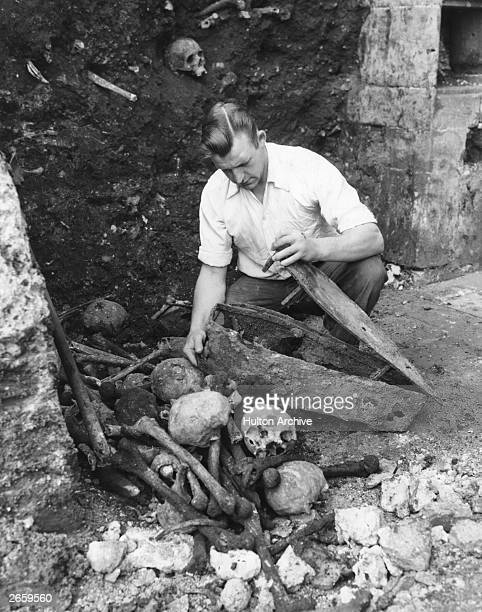 A demolition labourer with a coffin of a baby on a site discovered in a churchyard in the City of London where victims of the plague were buried in...