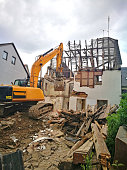 demolition of an old house with a chain excavator