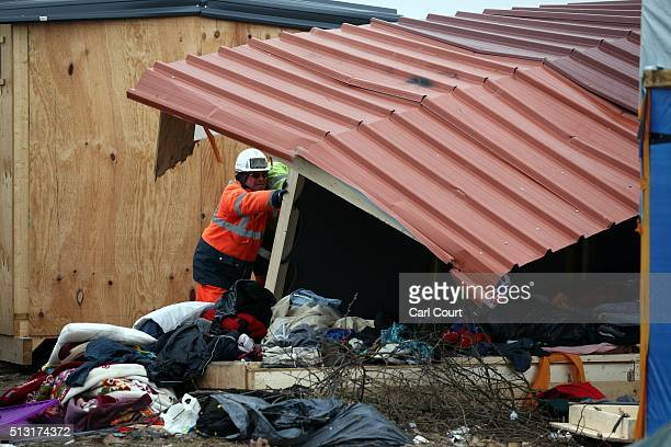 Demolition workers destroy a hut as they clear part of the 'jungle' migrant camp on March 01 2016 in Calais France Police and demolition teams are...
