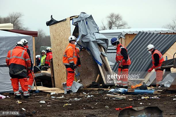 Demolition workers destroy huts as they clear part of the 'jungle' migrant camp on March 01 2016 in Calais France Police and demolition teams are...