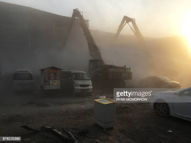 Demolition works take place at the site of a fatal housing block fire in Beijing on November 19 2017 Chinese authorities on November 19 launched an...
