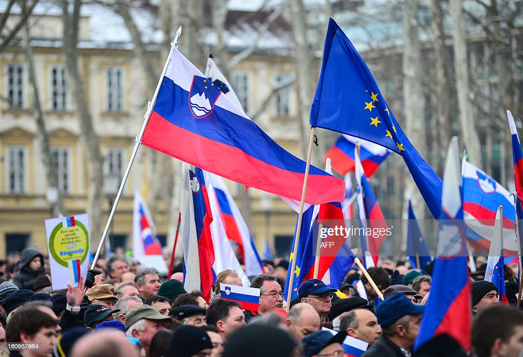 Demonastrators wave Slovenian and EU flags during a pro-government rally organised by the Assembly for the Republic, in support of Slovenian prime minister Janez Jansa on February 8, 2013 in Ljubljana's Congress Square. Slovenia's political crisis escalated on February 5 as a second partner left Prime Minister Janez Jansa's shaky coalition after he rejected the party's call to resign. AFP PHOTO/JURE MAKOVEC