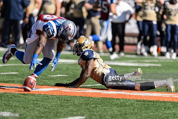 Demond Washington of the Winnipeg Blue Bombers watches as SJ Green of the Montreal Alouettes tries to pick up a loose ball during the CFL game at...