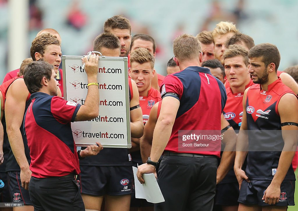 Demons coach Mark Neeld speaks to his team at three-quarter time as Jack Viney and Jimmy Toumpas of the Demons look on during the round one AFL match between the Melbourne Demons and Port Adelaide Power at the Melbourne Cricket Ground on March 31, 2013 in Melbourne, Australia.