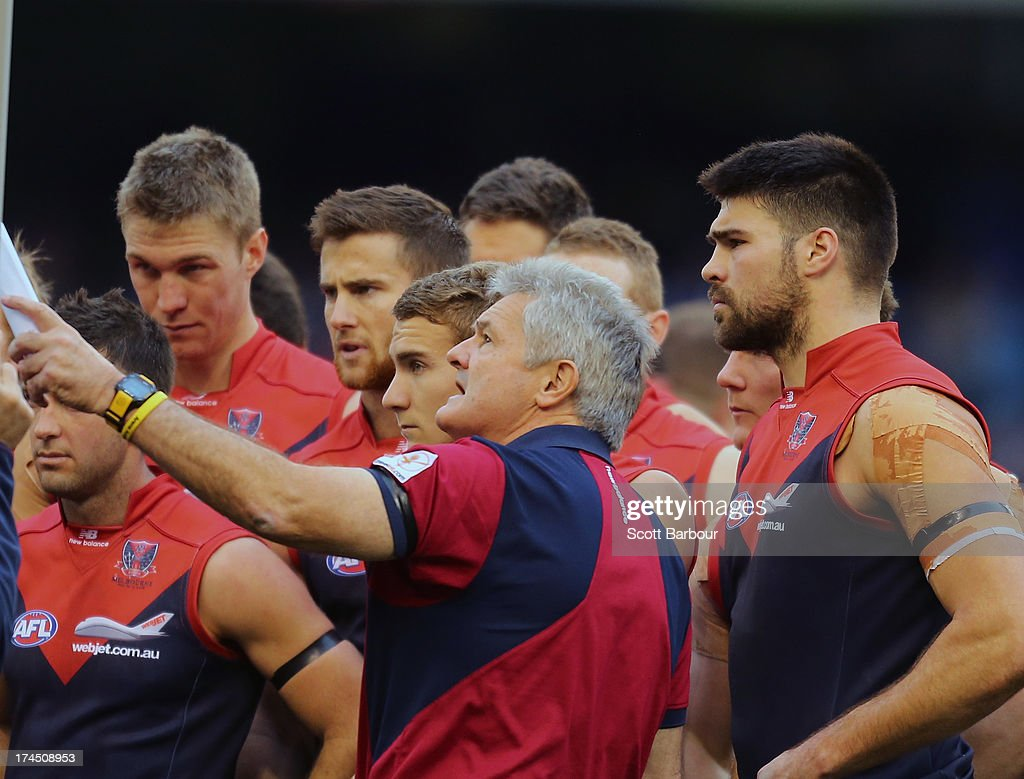 Demons coach Neil Craig speaks to his team as Chris Dawes looks on during the round 18 AFL match between the Melbourne Demons and the North Melbourne Kangaroos at Etihad Stadium on July 27, 2013 in Melbourne, Australia.