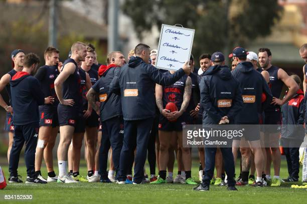 Demons coach Simon Goodwin speaks to his players during a Melbourne Demons AFL training session at Gosch's Paddock on August 18 2017 in Melbourne...