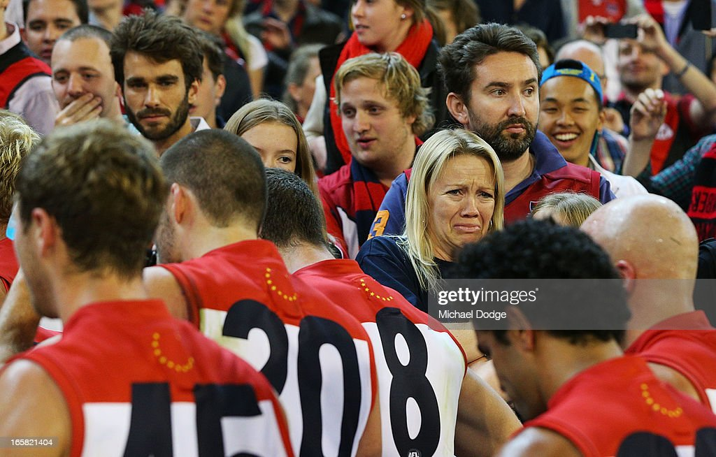 A Demons fan cries after the game as Demons players walk to the rooms after a big loss during the round two AFL match between the Essendon Bombers and the Melbourne Demons at Melbourne Cricket Ground on April 6, 2013 in Melbourne, Australia.