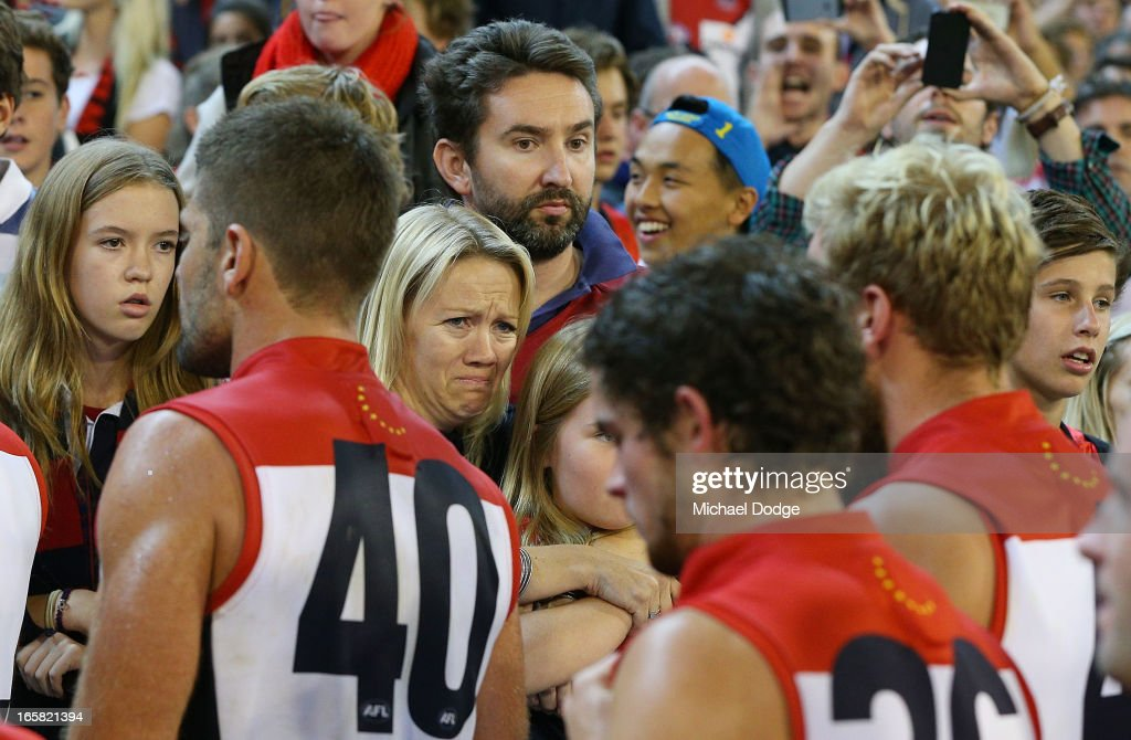 A Demons fan cries after the game as Mark Jamar walks to the rooms after a big loss during the round two AFL match between the Essendon Bombers and the Melbourne Demons at Melbourne Cricket Ground on April 6, 2013 in Melbourne, Australia.