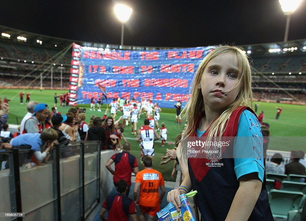 A Demons fan looks on as players run through the banner during the round two AFL match between the Essendon Bombers and the Melbourne Demons at Melbourne Cricket Ground on April 6, 2013 in Melbourne, Australia.