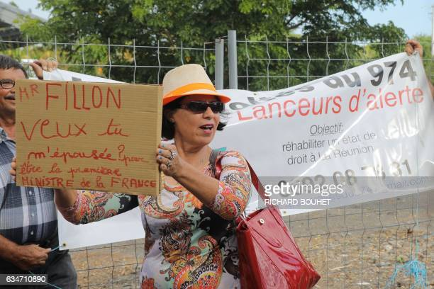 A demonstator holds a sign reading 'Francois Fillon do you want to marry me To become France's Prime minister' as French presidential election...