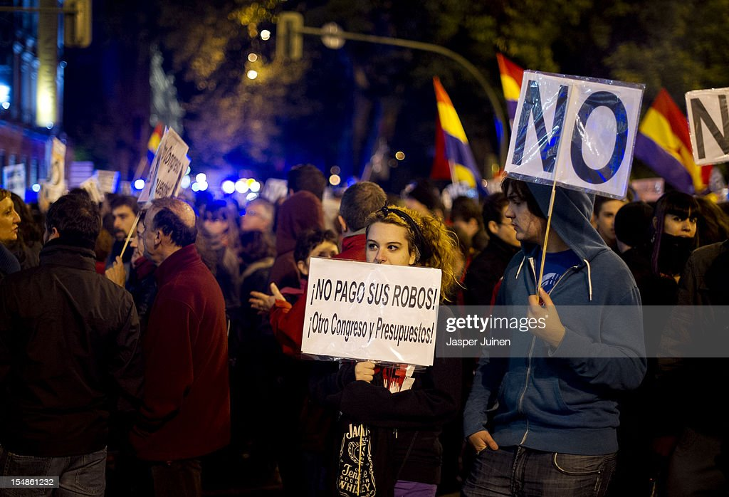 A demonstrater holds a banner reading 'I am not paying their robberies, another congress and budgets' during a protest against spending cuts and the government of Mariano Rajoy on October 27, 2012 in Madrid, Spain. Demonstrators are protesting near the Spanish Parliament against the government's austerity measures. With the economic crisis tightening it's grip, Spain is in its second recession in three years, Rajoy's governement is presssured more and more to seek aid that can easy their debts.