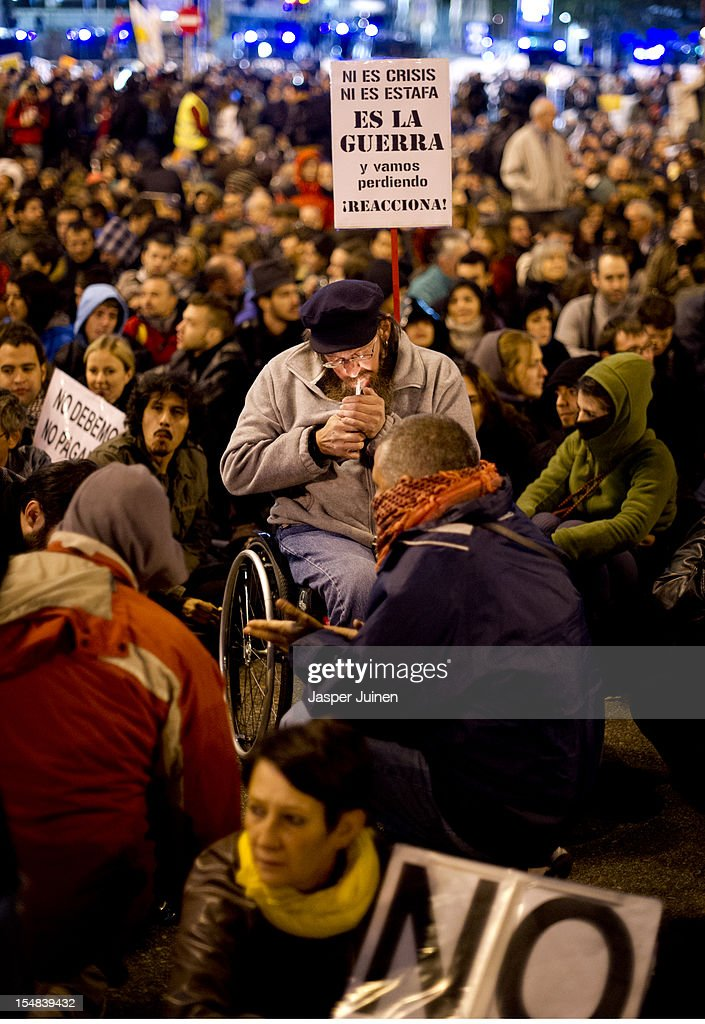 A demonstraters in a wheelchair lites a cigarette while holding a banner reading 'Not a crisis, not a fraud, it's a war and we are going to lose; react!' during a protest against spending cuts and the government of Mariano Rajoy on October 27, 2012 in Madrid, Spain. Demonstrators are protesting near the Spanish Parliament against the government's austerity measures. With the economic crisis tightening it's grip, Spain is in its second recession in three years, Rajoy's governement is presssured more and more to seek aid that can easy their debts.