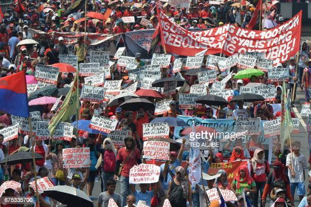Demonstrating Philippine workers displaying placards and streamers march towards a park during a May Day rally in Manila on May 1 2017 / AFP PHOTO /...