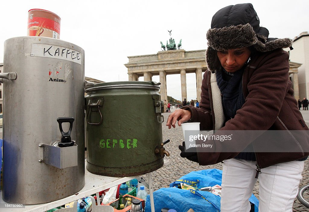 A demonstrating refugee from Iran fills a cup with water for tea during a hunger strike in front of the Brandenburg Gate on October 25, 2012 in Berlin, Germany. The demonstrators, predominantly from Iran, Afghanistan and Iraq are subsisting on only water, tea and coffee without sugar, and claim to have been told by the police that they are not allowed blankets or tents. They have been sitting in front of the Brandenburg Gate since last night, and say they will continue their strike until the German government responds to their demands for a halt to deportations and faster processing of asylum applications.