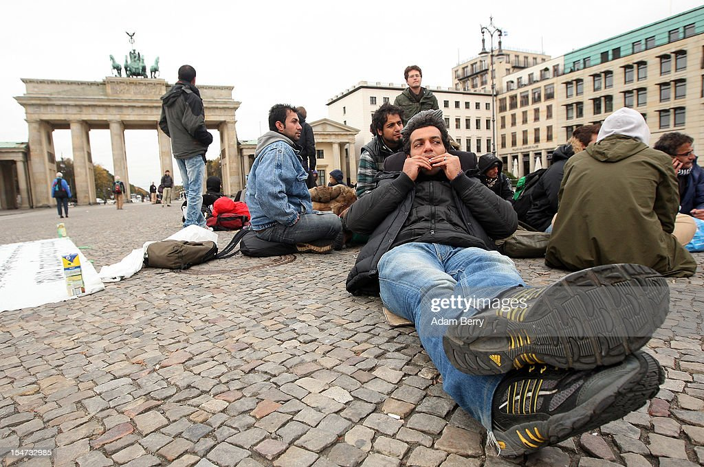 A demonstrating refugee from Iran rolls a cigarette while lying on the ground during a hunger strike in front of the Brandenburg Gate on October 25, 2012 in Berlin, Germany. The demonstrators, predominantly from Iran, Afghanistan and Iraq are subsisting on only water, tea and coffee without sugar, and claim to have been told by the police that they are not allowed blankets or tents. They have been sitting in front of the Brandenburg Gate since last night, and say they will continue their strike until the German government responds to their demands for a halt to deportations and faster processing of asylum applications.