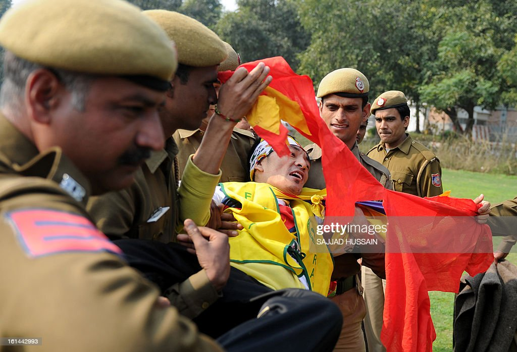 A demonstrating Tibetan exile tears a Chinese flag while being detained by Indian police outside the Chinese embassy during Losar, the Tibetan new year, in New Delhi on February 11, 2013. Lobsang Sangay, the Tibetan prime minister in exile, has called for traditional Losar (the Tibetan new year) celebrations to be shelved as a mark of respect to the nearly 100 people who have set themselves on fire in the last three years. AFP PHOTO/ SAJJAD HUSSAIN