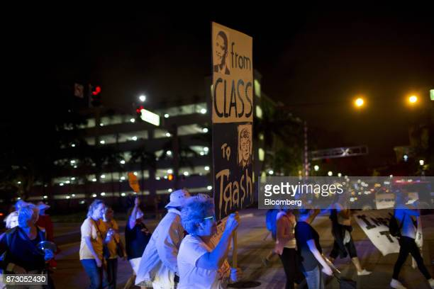 A demonstration holds a sign reading 'From Class To Trash' during a protest on the one year anniversary of the first antiTrump rally in West Palm...