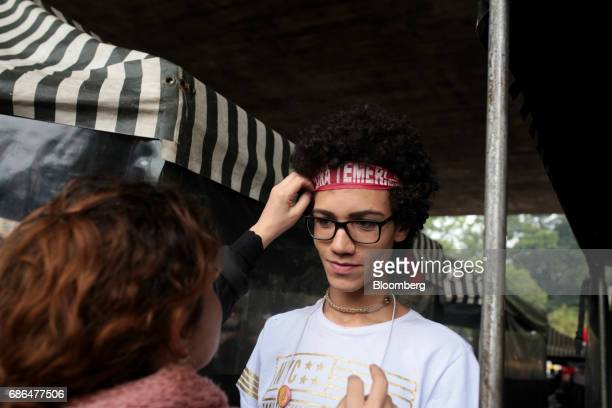 A demonstrator adjusts a headband that reads 'Out Temer' during a protest against Brazilian President Michel Temer and a demand for new elections on...