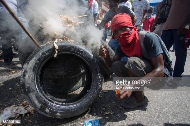 A demonstrator against the government of Haitian President Jovenel Moise set a tire ablaze in PortauPrince on October 17 2017 Haitian police on...