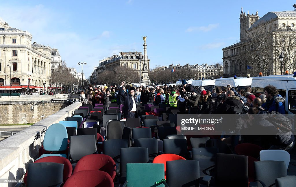 A demonstrator among chairs taken from bank offices gestures on February 8, 2016 on the pont au change near the Court of Paris during a demonstration against bank system and tax fraud, as former French budget minister Jerome Cahuzac goes on trial on February 8 for tax fraud. Cahuzac resigned in disgrace in 2013 after admitting to having a secret Swiss bank account, and faces up to seven years in jail and two million euros ($2.2 million) in fines. AFP PHOTO / MIGUEL MEDINA / AFP / MIGUEL MEDINA