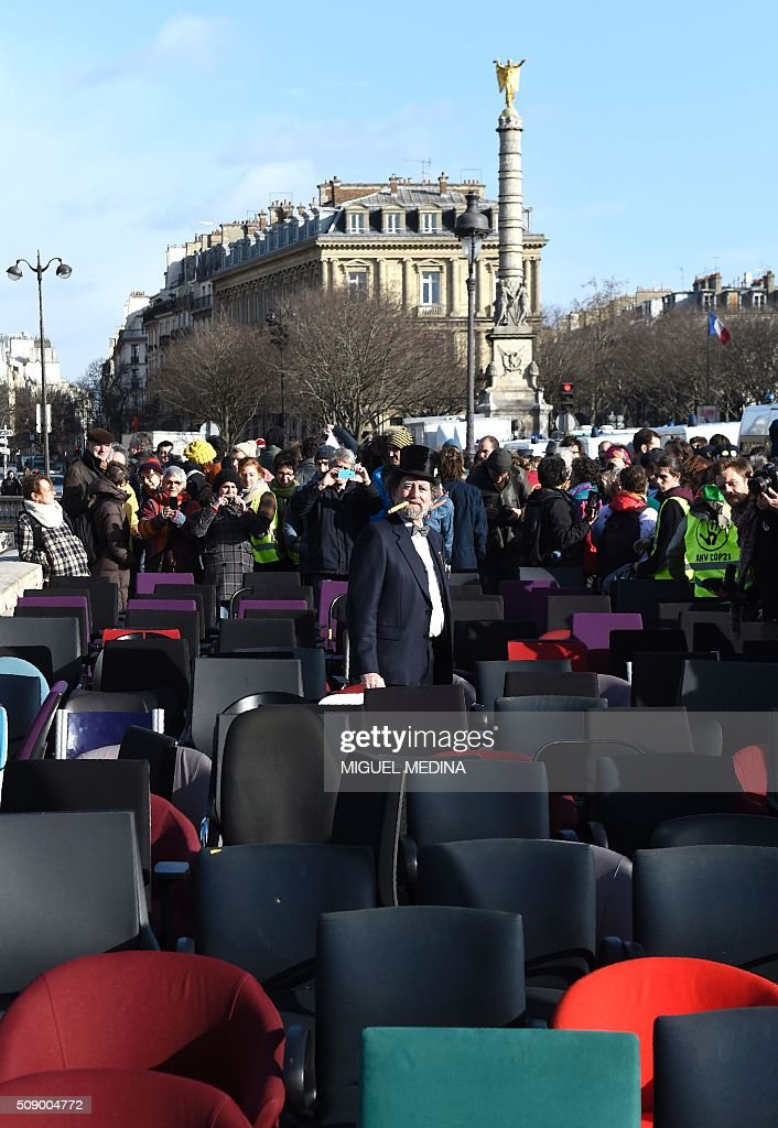 A demonstrator among chairs taken from bank offices poses on February 8, 2016 on the pont au change near the Court of Paris during a demonstration against bank system and tax fraud, as former French budget minister Jerome Cahuzac goes on trial on February 8 for tax fraud. Cahuzac resigned in disgrace in 2013 after admitting to having a secret Swiss bank account, and faces up to seven years in jail and two million euros ($2.2 million) in fines. AFP PHOTO / MIGUEL MEDINA / AFP / MIGUEL MEDINA