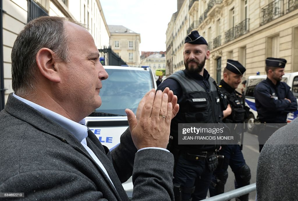 A demonstrator applauses the police in support of their action, during a protest demanding the unionists to stop 'blocking the economy and employment' in the context of the mobilisation against the labour law before the Loire-Atlantic prefecture, in Nantes, northwestern France, on May 27, 2016. Around 150 shopkeepers, company heads and unionists from the employers federation gathered on May 27, 2016, in front of the Loire-Atlantic prefecture to demande the workers unionists to stop 'blocking the economy and employment' in the context of the mobilisation against the labour law. / AFP / JEAN