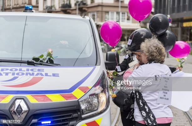 A demonstrator bearing a sign reading 'Careful for my husband proud of my husband' stands next to a police car during a protest of law enforcement's...