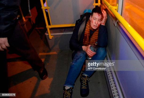 TOPSHOT A demonstrator bleeds after being detained by police officers during an unauthorized rally in Saint Petersburg on October 7 2017 Several...