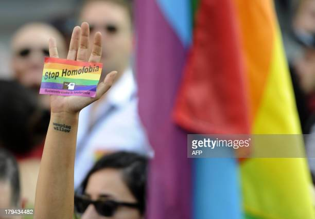 A demonstrator brandishes a rainbow flag sticker as he protests against homophobia and repression against gays in Russia outside the Ministry of...