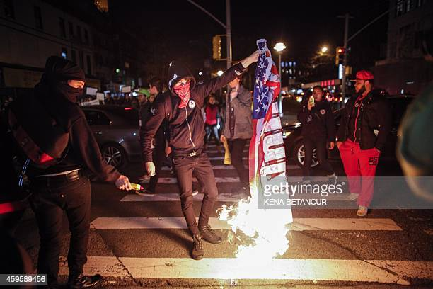 A demonstrator burns an American flag during a protest November 25 2015 in New York City one day after a grand jury decision not to prosecute a white...