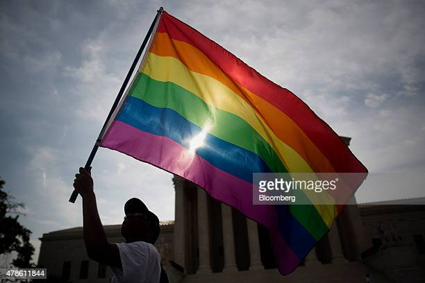Demonstrator Carlos McKnight from Washington DC waves a rainbow flag outside the US Supreme Court in Washington DC US on Friday June 26 2015 The high...