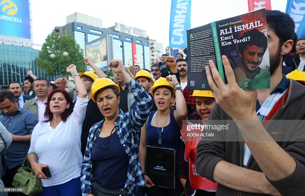 A demonstrator carries a book titled, 'Ali Ismail: Who gave the order?' as protestors gesture and shout slogans on May 31, 2016 in Ankara during a demonstration commemorating the third anniversary of the start of the Gezi Park protests. The Gezi Park protests which began in May 2013, were sparked by the heavy-handed eviction of demonstrators staging a sit-in protest against the redevelopment of the area and grew into often violent clashes with police as people demonstrated against much broader issues concerning perceived infringements of civil rights. / AFP / ADEM