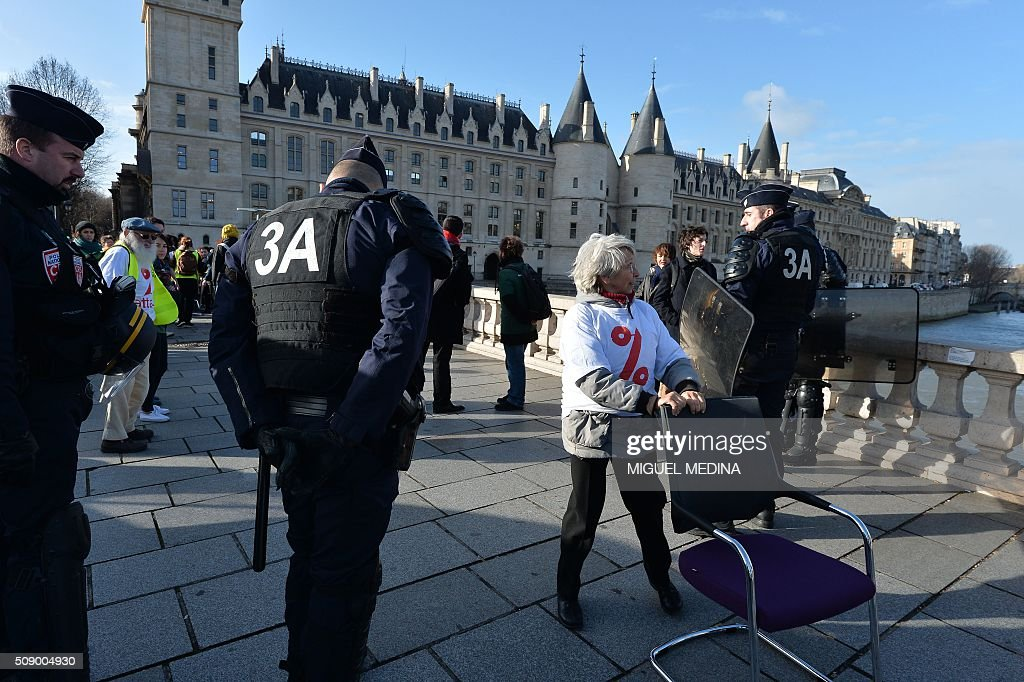 A demonstrator carries a chair taken from bank offices next to policemen on February 8, 2016 on the pont au change near the Court of Paris during a demonstration against bank system and tax fraud, as former French budget minister Jerome Cahuzac goes on trial on February 8 for tax fraud. Cahuzac resigned in disgrace in 2013 after admitting to having a secret Swiss bank account, and faces up to seven years in jail and two million euros ($2.2 million) in fines. AFP PHOTO / MIGUEL MEDINA / AFP / MIGUEL MEDINA