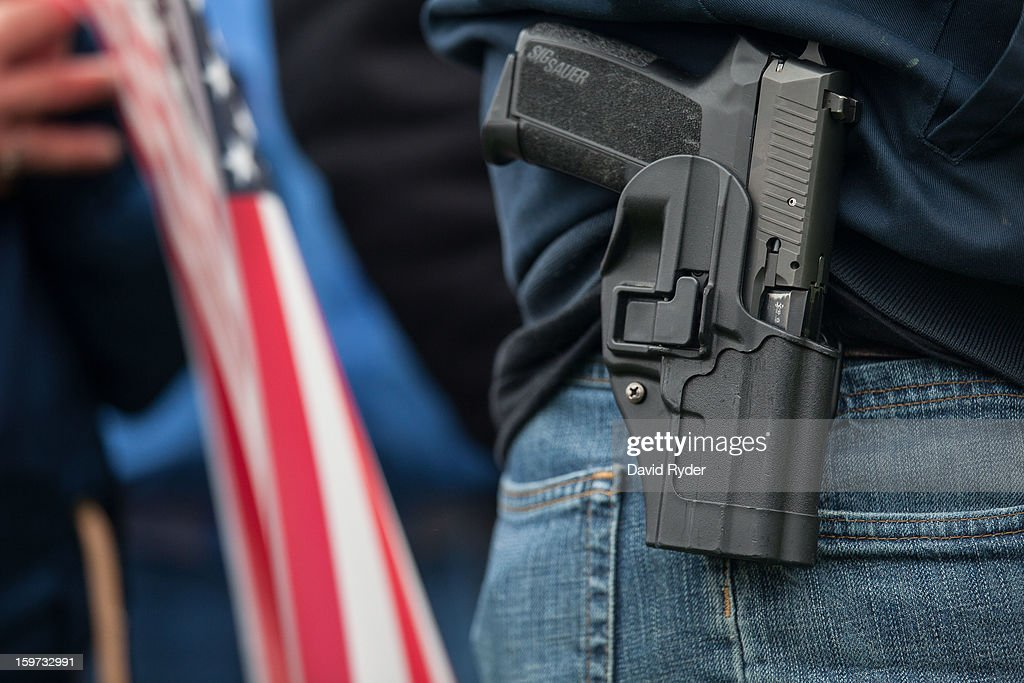 A demonstrator carries a handgun while listening to speakers at a pro-gun rally on January 19, 2013 in Olympia, Washington. The Guns Across America national campaign drew thousands of protesters to state capitols, including over 1,000 in Olympia.
