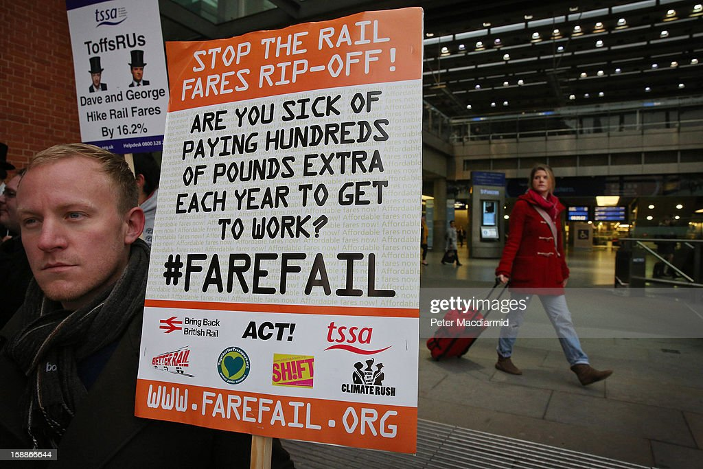 A demonstrator carries a placard protesting rail fare increases outside St Pancras station on January 2, 2013 in London, England. Rail fares have today risen by an average of 4.2% in England, Scotland and Wales, the tenth year in a row that fares have increased above inflation.