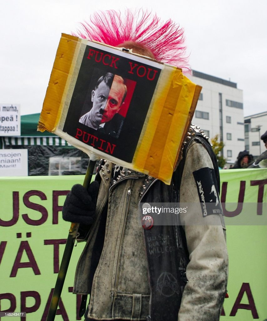 A demonstrator carries a placard representing a 'two-faced' Russian President Vladimir Putin as Hitler in front of the Sibelius-hall in Lahti 20 October 2006. The European Union informal meeting of heads of state or government was followed by a working dinner with Putin against a backdrop of growing European concerns about Russia's use of its energy resources and human rights.